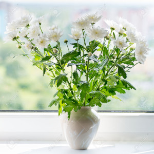 Vase with a flower white chrysanthemum on the windowsill